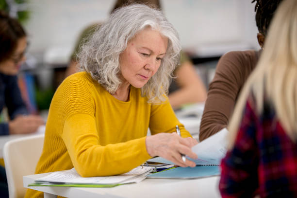 Senior Woman Studying A group of university students are indoors in a study hall. A senior woman is looking through her notes in preparation for a test. adult learning stock pictures, royalty-free photos & images