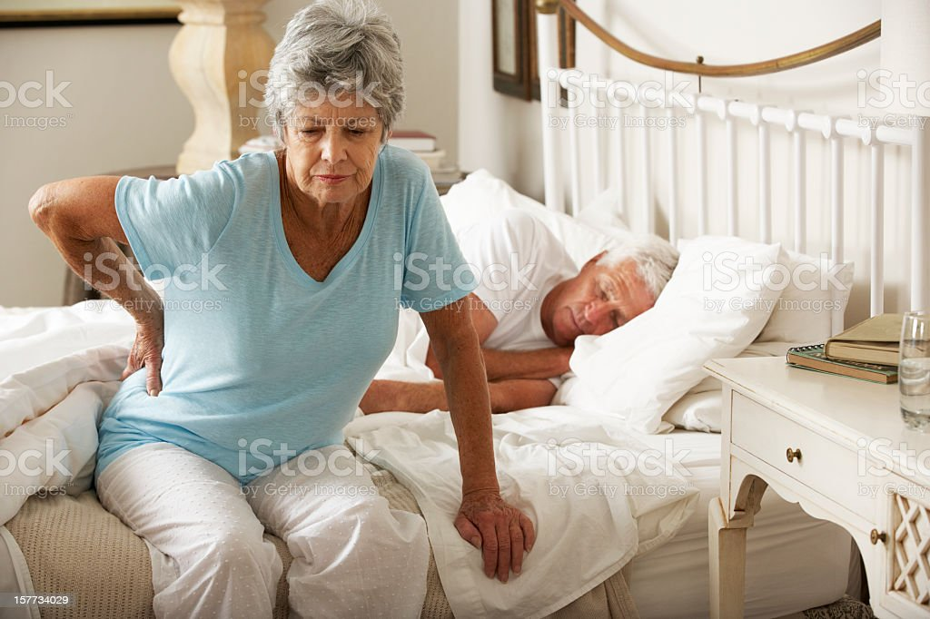Senior Woman Suffering From Backache Getting Out Of Bed stock photo