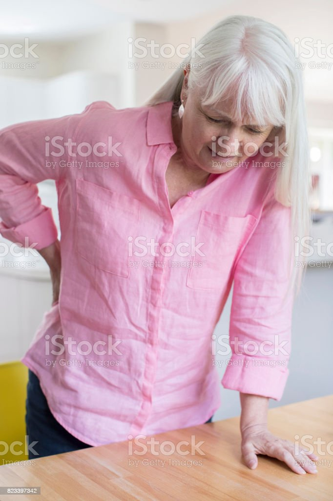 Senior Woman Suffering From Backache Whilst Getting Out Of Chair At Home stock photo