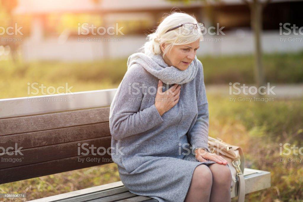 벤치에 앉아있는 동안 가슴 통증에서 고통 고위 여자 - 로열티 프리 가슴통증 스톡 사진