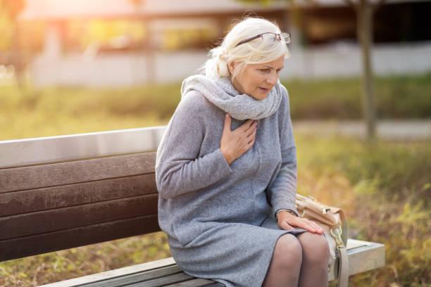 Senior mulher sofre de dores no peito enquanto está sentado no banco - foto de acervo