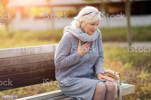 벤치에 앉아있는 동안 가슴 통증에서 고통 고위 여자 가슴통증에 대한 스톡 사진 및 기타 이미지