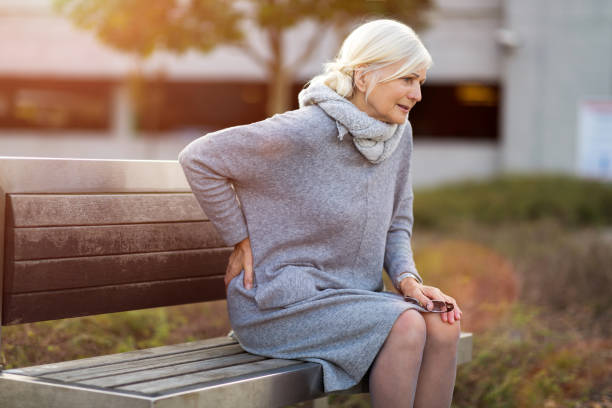 senior woman suffering from chest pain while sitting on bench - backache stock pictures, royalty-free photos & images