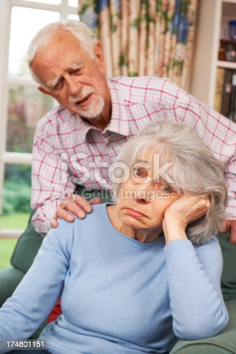 874789476istockphoto Senior Woman Suffering From Depression Comforted By Husband 174801151