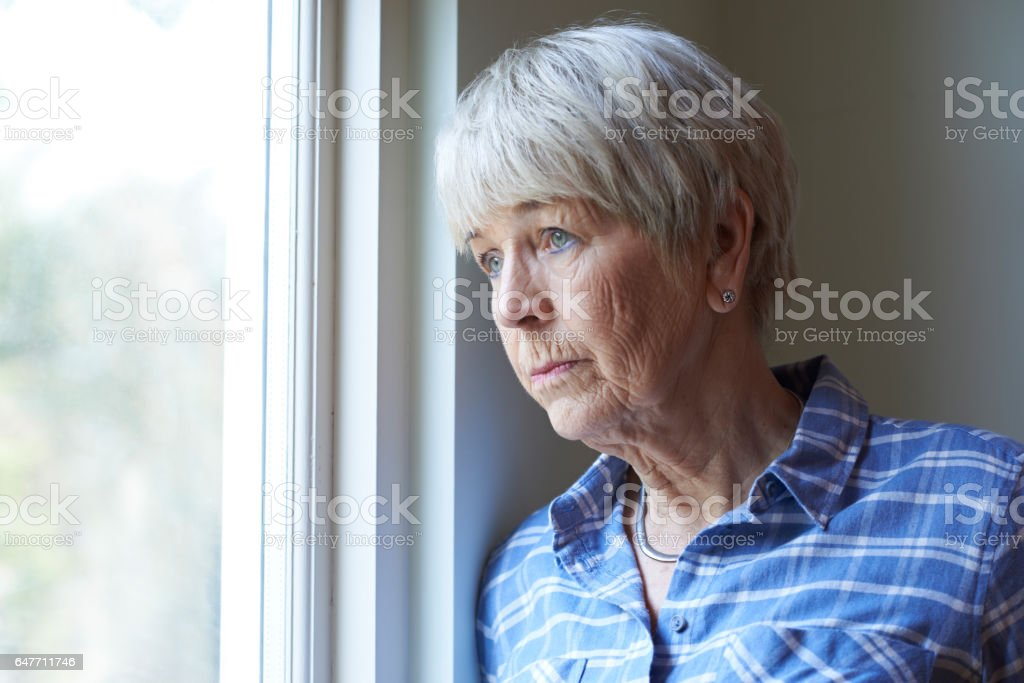 Senior Woman Suffering From Depression Looking Out Of Window stock photo