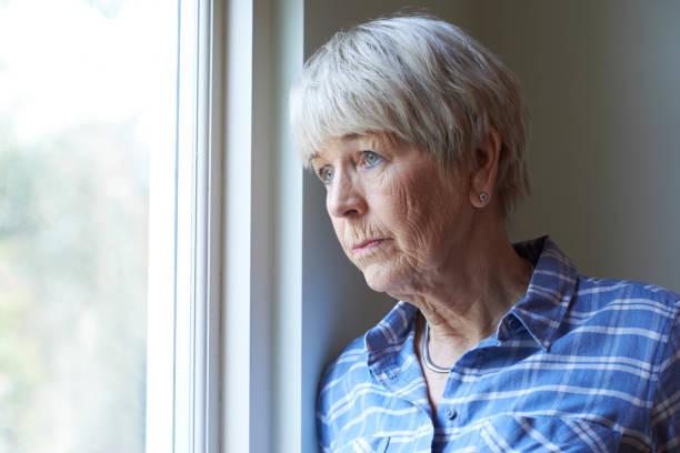Senior mulher sofre de depressão, olhando pela janela - foto de acervo