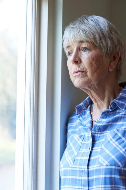 Mujer Senior que sufre de depresión mirando por la ventana - foto de stock
