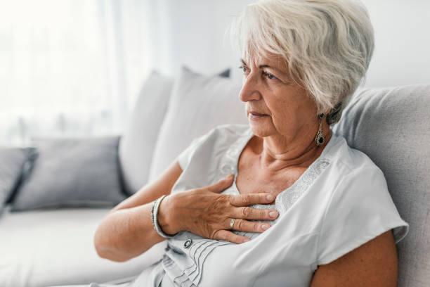 senior kvinna lider av halsbränna eller bröst obehag symptom - matsmältningsbesvär bildbanksfoton och bilder