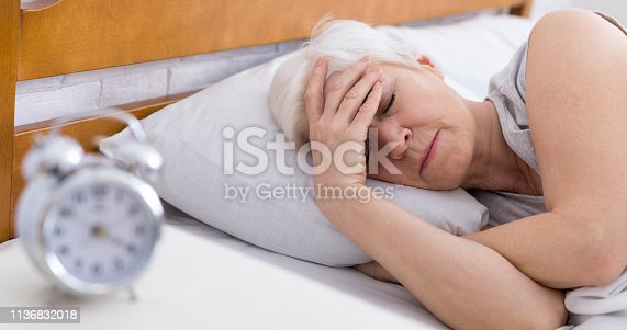 Worried senior woman suffering from insomnia, having headache in bed, touching her forehead, panorama