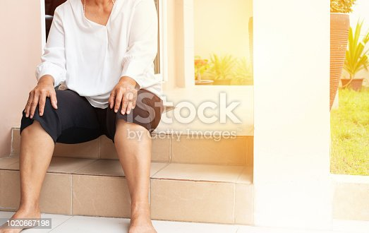 698466046 istock photo senior woman suffering from knee pain at home, health problem concept 1020667198