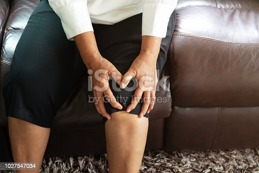 698466046 istock photo senior woman suffering from knee pain at home, health problem concept 1027547034