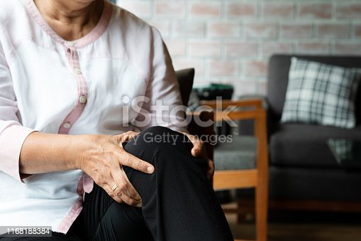 698466046 istock photo senior woman suffering from knee pain at home, health problem concept 1168188384