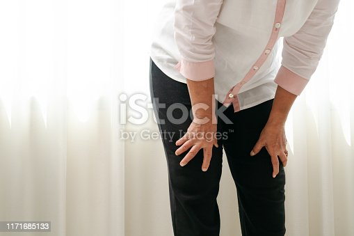 698466046 istock photo senior woman suffering from knee pain at home, health problem concept 1171685133