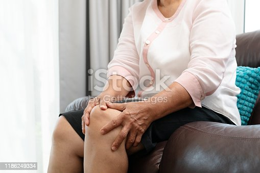 875123630 istock photo senior woman suffering from knee pain at home, health problem concept 1186249334