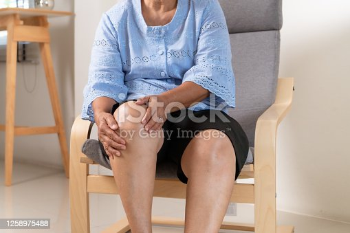 875123630 istock photo senior woman suffering from knee pain at home, health problem concept 1258975488