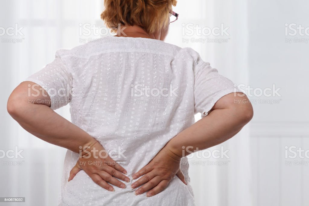 Senior woman suffering from low back pain. Chiropractic, osteopathy, Physiotherapy. Alternative medicine, pain relief concept. stock photo