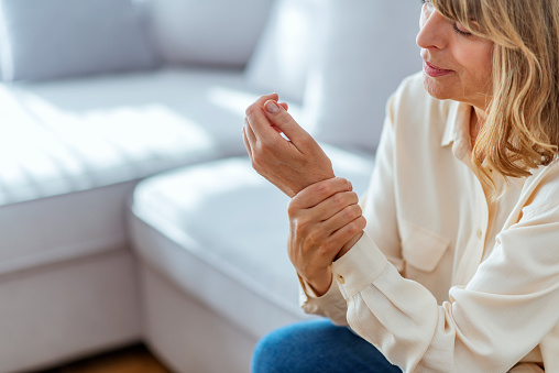 istock Senior woman suffering from pain in hand at home 1153388668