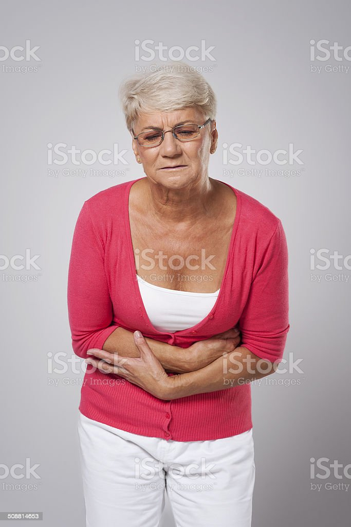 Senior woman suffering from stomach ache stock photo