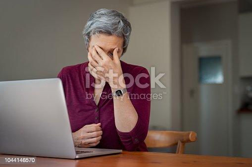 istock Senior woman suffering headache after work 1044146570