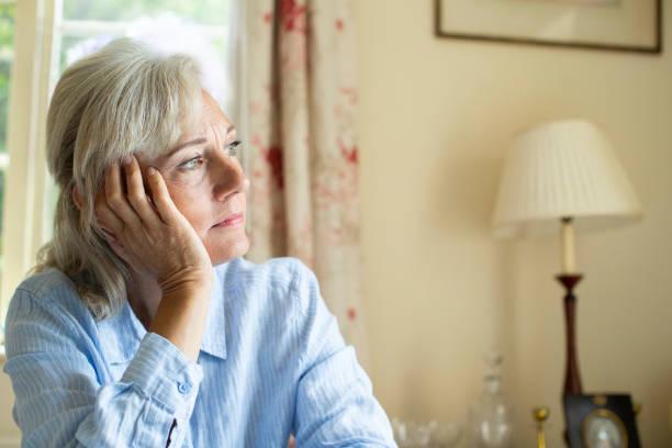 Senior Woman, die mit Depressionen zu Hause das Fenster aussucht – Foto