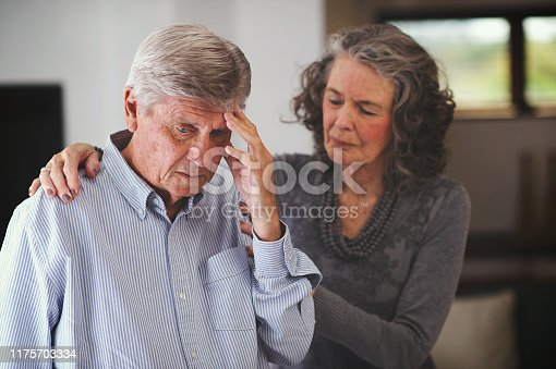 istock Senior woman supporting a man who has received bad news hand on shoulder 1175703334