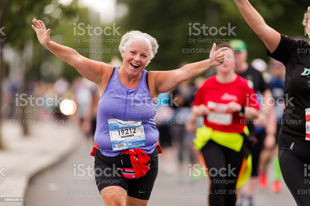 Senior woman takes part in half marathon stock photo