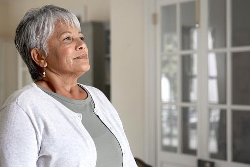 Portrait of beautiful senior woman taking a deep breath in her kitchen
