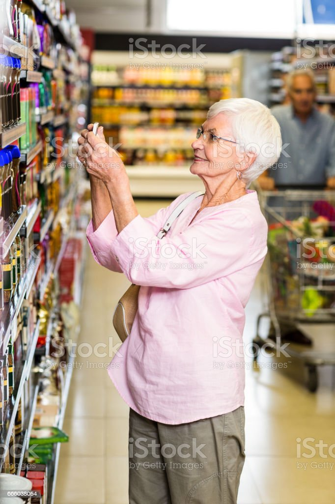Senior woman taking a picture of product on shelf stock photo