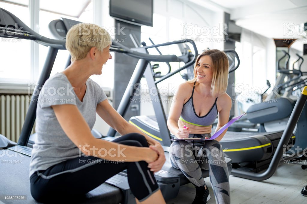 Beautiful young female fitness instructor with her senior woman...