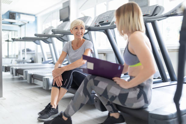 senior woman taking advices from her fitness coach - runner rehab gym foto e immagini stock