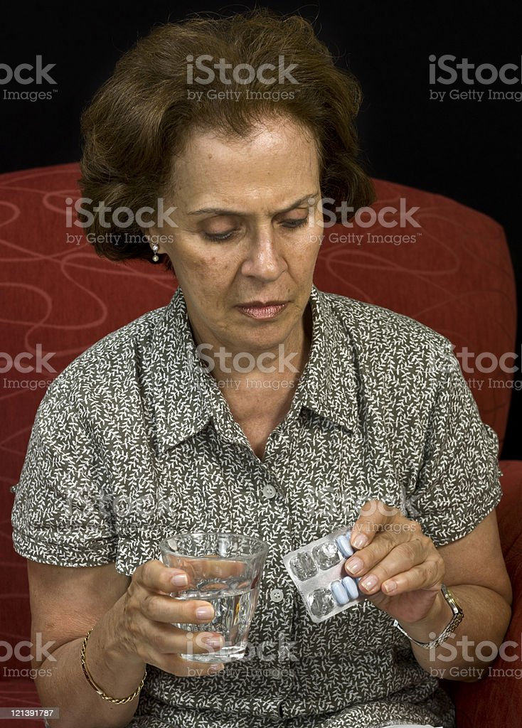 Senior woman taking her medicine royalty-free stock photo