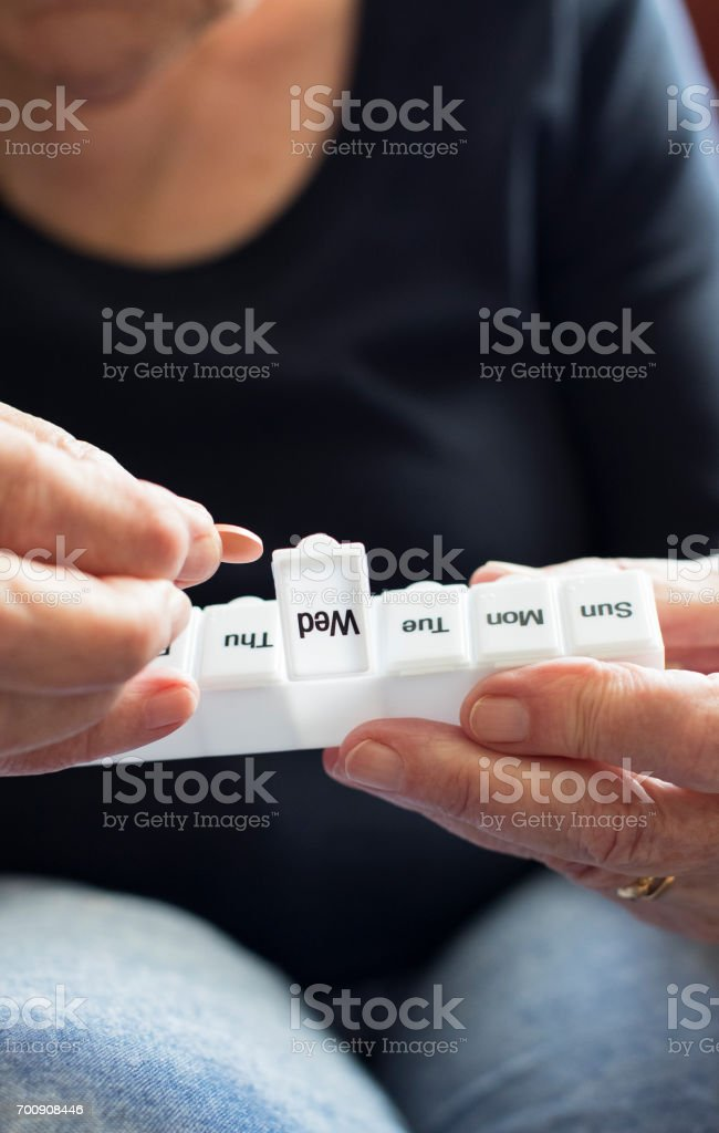 Senior Woman Taking Medication From Pill Box stock photo