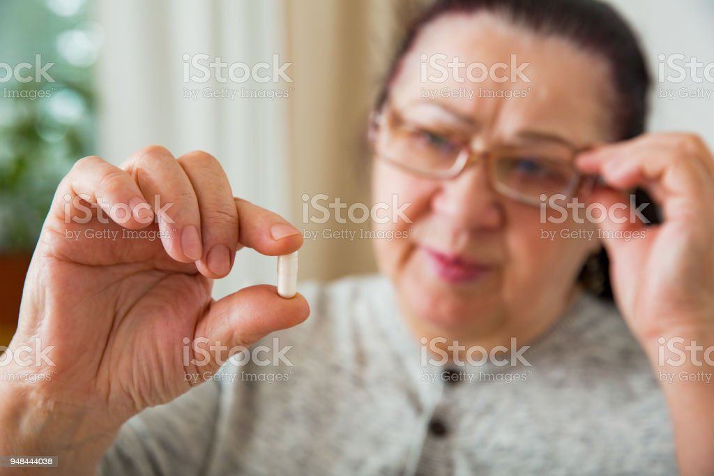 Senior Woman Taking Medication, holding pill in hand, looking though glasses. Elderly Person reading prescription on medicine bottle. stock photo