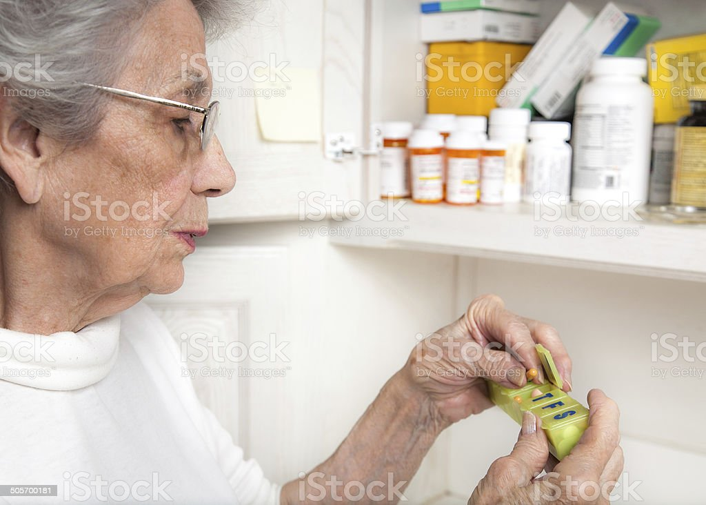 senior woman taking medicine from pill organizer stock photo