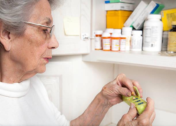 senior woman taking medicine from pill organizer stock photo
