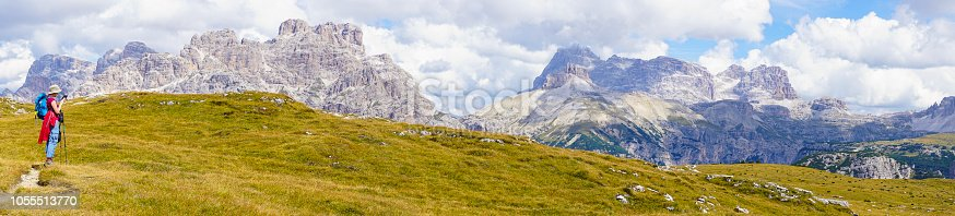 Senior woman taking  panorama view photo of Dolomites from World War I tranches on Mount Piana which is 2324 m Hight. It is part of Dolomites mountain range located in northeastern Italy and are on the list of  UNESCO World Heritage Sites.