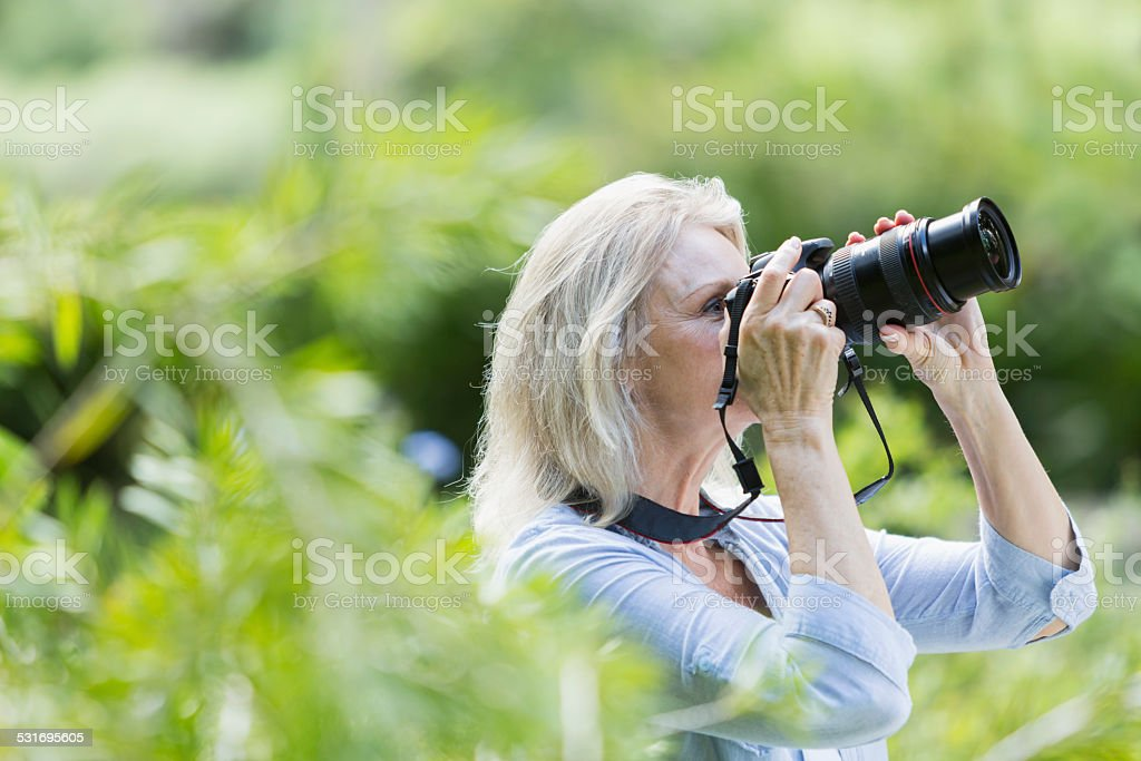 Senior woman taking photographs with camera stock photo