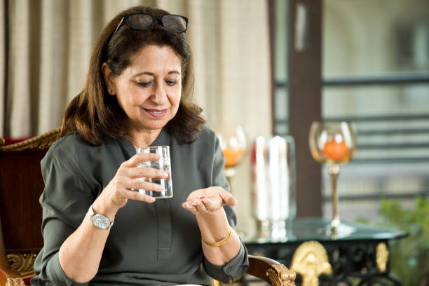 Senior woman taking pill Senior woman taking pill with water at home woman taking pills stock pictures, royalty-free photos & images