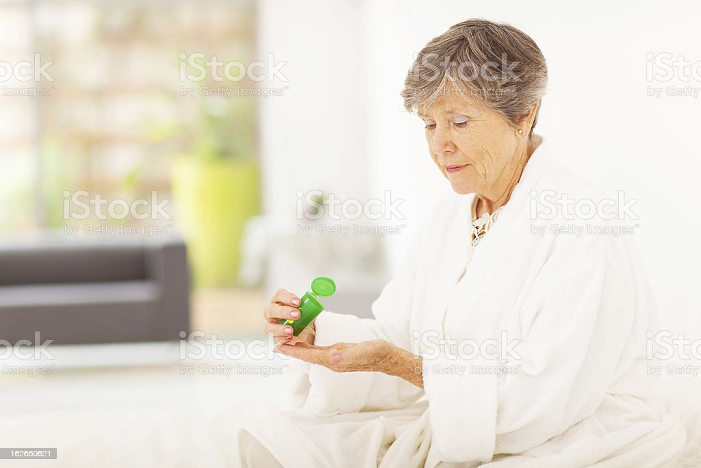 senior woman taking pills senior woman taking pills at home 70-79 Years Stock Photo