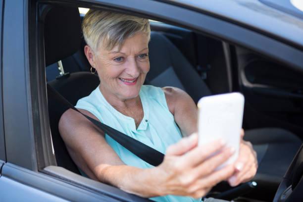 Senior woman taking selfie with mobile phone stock photo