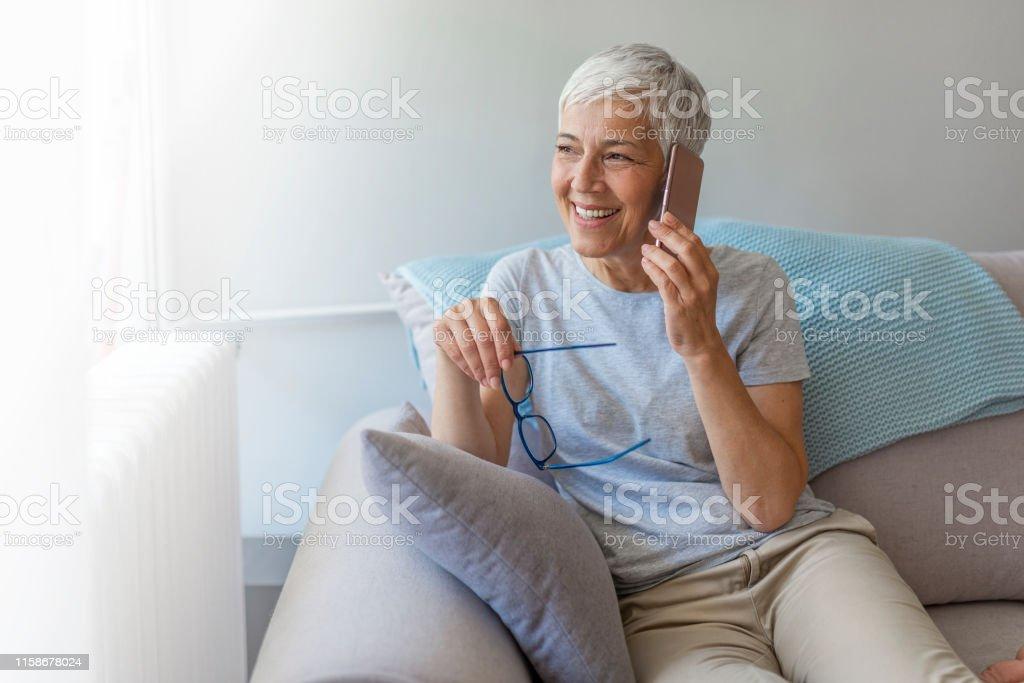 그녀의 휴대 전화에 이야기 하는 선임 여자. - 로열티 프리 70-79세 스톡 사진