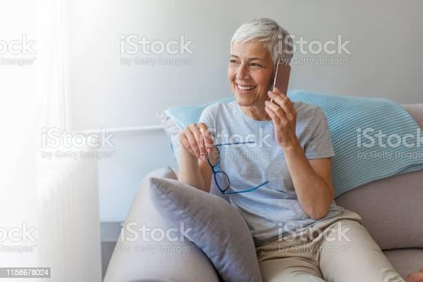 그녀의 휴대 전화에 이야기 하는 선임 여자 70-79세에 대한 스톡 사진 및 기타 이미지