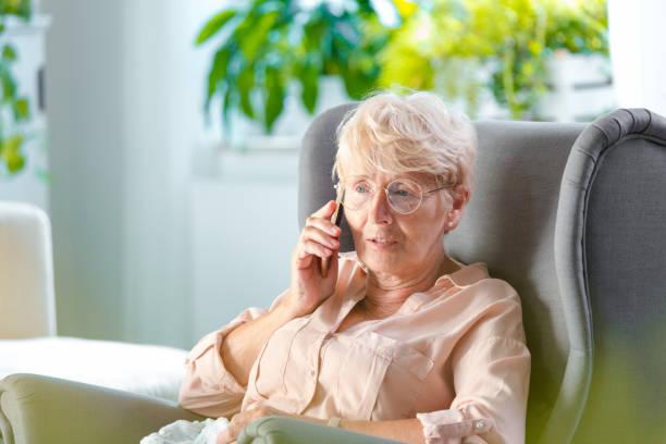 femme aîné parlant sur le téléphone portable - seulement des femmes seniors photos et images de collection