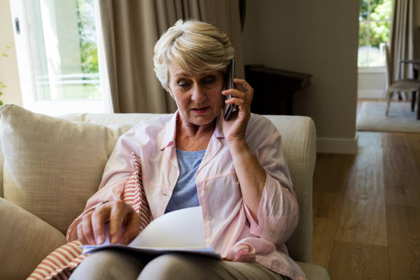 senior woman talking on mobile phone while checking a document in living room - older woman phone stock photos and pictures