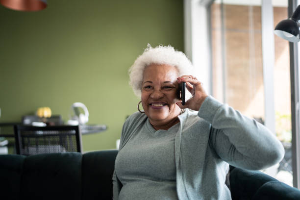 Senior woman talking on the phone at home stock photo