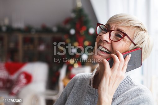 Smiling senor woman sitting in her living room and enjoying while talking on mobile phone.