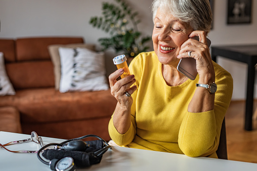 Photo of senior woman at home preparing to drink medical pill. She is holding a pill bottle and talking on the phone with a doctor