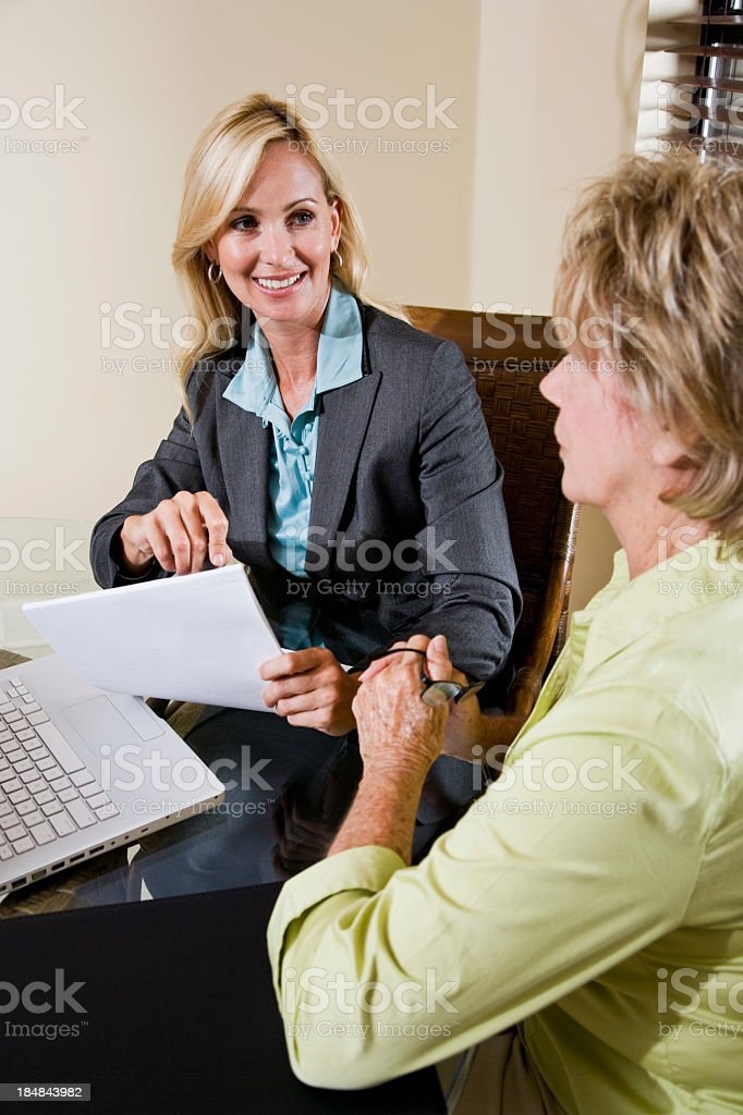 Senior woman talking with financial planner or consultant stock photo