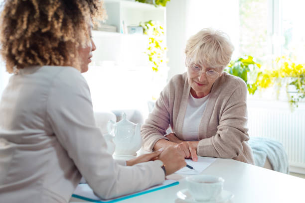 Ältere Frau im Gespräch mit Versicherungsberater – Foto