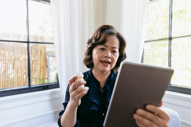 mujer senior habla con un médico en línea - telehealth fotografías e imágenes de stock